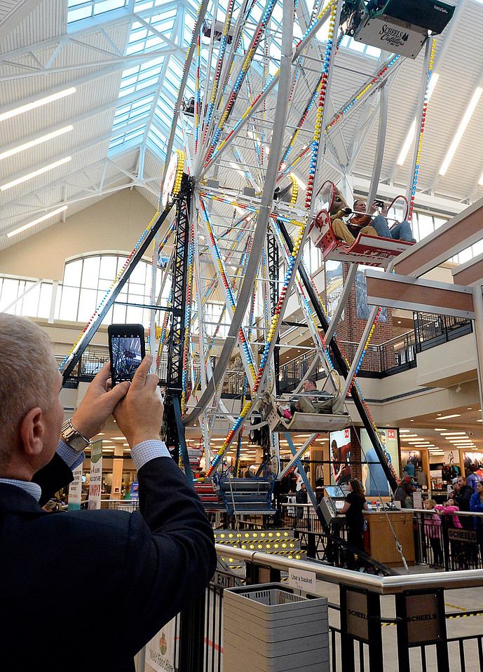 Chris Ferris, left, senir associate athletic director for CSU, takes a photo of Johnstown Mayor Scott James riding the ferris wheel with Colorado State University's mascot, Cam the Ram on Thursday, Oct. 26, 2017,      at Scheels in Johnstown. Scott plans to ride the Scheels Ferris Wheel for 50 hours straight to raise money for the Larimer and Weld Food Banks. He will ride night and day with a five minute restroom break every hour and a 15 minute stretching break every four hours, Thursday to Saturday.  (Photo by Jenny Sparks/Loveland Reporter-Herald)