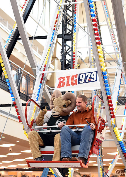 Johnstown Mayor Scott James, right, rides the ferris wheel with Colorado State University's mascot, Cam the Ram on Thursday, Oct. 26, 2017,      at Scheels in Johnstown. Scott plans to ride the Scheels ferris wheel for 50 hours straight to raise money for the Larimer and Weld Food Banks. He will ride night and day with a five minute restroom break every hour and a 15 minute stretching break every four hours, Thursday to Saturday.  (Photo by Jenny Sparks/Loveland Reporter-Herald)