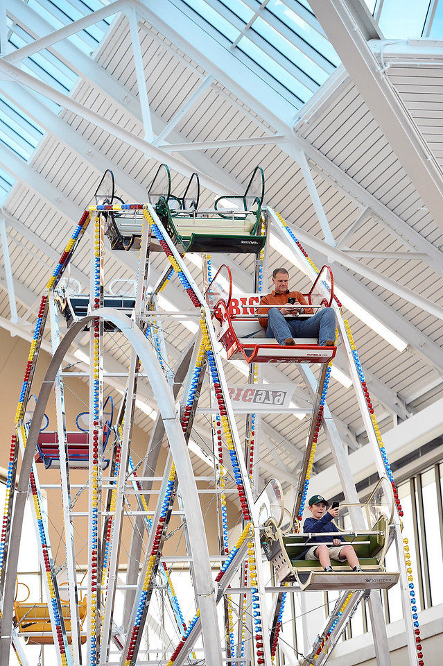 Johnstown Mayor Scott James, top, rides the Scheels ferris wheel as Mason Newman, 12, below, takes a selfie as he rides Thursday, Oct. 26, 2017, in Johnstown. Scott plans to ride the Scheels ferris wheel for 50 hours straight to raise money for the Larimer and Weld Food Banks. He will ride night and day with a five minute restroom break every hour and a 15 minute stretching break every four hours, Thursday to Saturday.  (Photo by Jenny Sparks/Loveland Reporter-Herald)