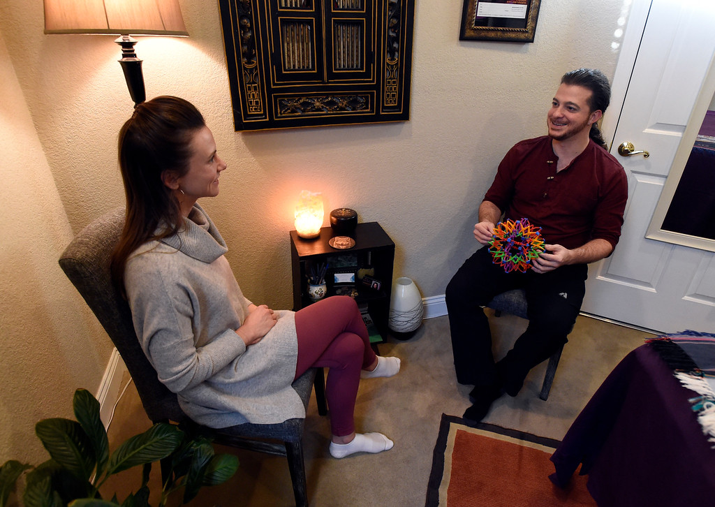 . LAFAYETTE, CO - NOVEMBER 19, 2018: Licensed Massage Therapist Jonathan Grassi, right, talks with Katie McDonald, of Westminster, before her massage appointment on Monday at Inner Ocean Center for Healing in Lafayette. For more photos of Grassi at work go to dailycamera.com (Photo by Jeremy Papasso/Staff Photographer)