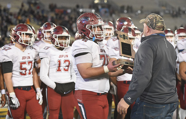 Joplin senior Logan Myers accepts the second place tophy after the Class 6 Championship game on Saturday in Columbia.<br /> Globe | Laurie Sisk