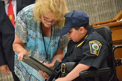 John Brewer - Oneida Daily Dispatch Make-A-Wish recipient Jordan Barahmeh signs his name to become an honorary Oneida City Police officer on Tuesday, Aug. 29, 2017. With him is Oneida City Clerk Sue Pulverenti.