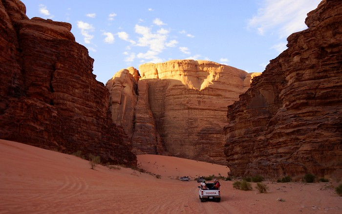 Off-roading between massive rock formations in Wadi Rum, Jordan.