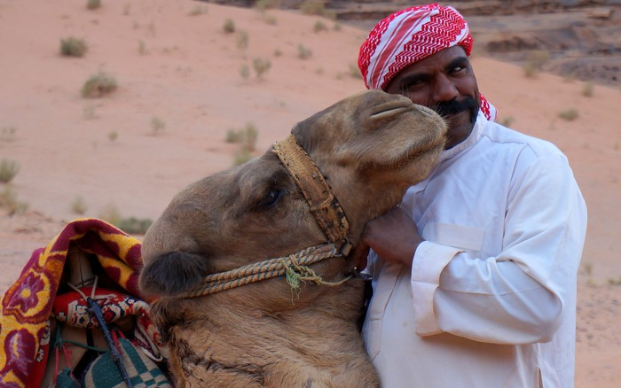A Bedouin guide kissing his camel in Wadi Rum, Jordan.