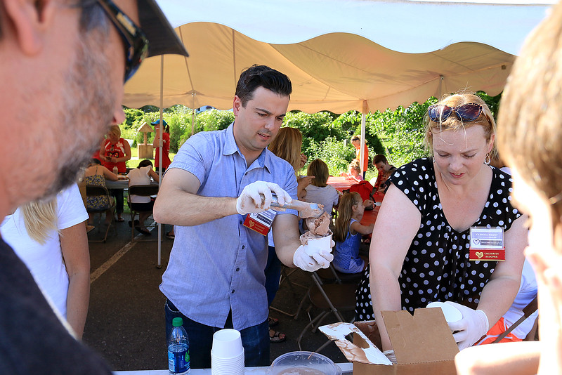Chris Lambert the Channel 7 weatherman and Sabrina Heisey a member of the Dracut School Committee scoop ice cream at the Joseph Middlemiss Big Heart Foundation's 4th annual Celebrity Scoop Fest at Shaw Farm in Dracut. SUN/JOHN LOVE