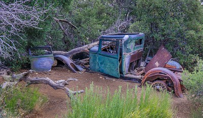 Old car was left in a flash flood wash, causing the vehicle to get partially covered in gravel over time.