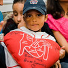 Josmaily Luzon Cruz, 6, held by mom Jasmin Luzon, smiles as he looks down at a stuffed heart signed by David Ortiz during a pre-game ceremony held on Sunday afternoon, Ortiz's last home game as a member of the Boston Red Sox. Cruz receiving life-saving heart surgery paid for through the David Ortiz Children's Fund in September 2014. SENTINEL & ENTERPRISE / Ashley Green