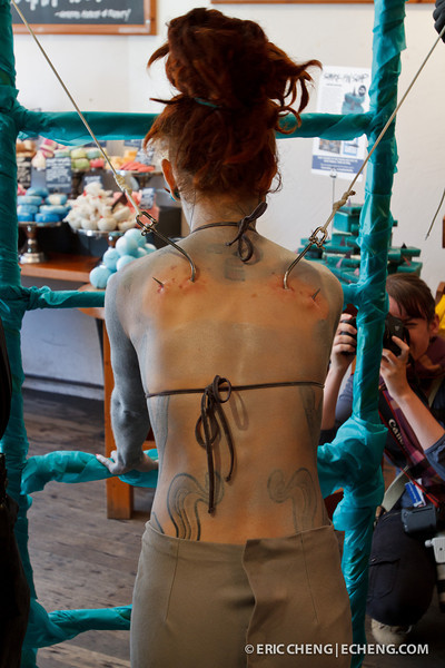 Performance artist Alice Newstead preps to be hung by shark hooks
