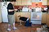 Alex, the taskmaster, watches Julie clean the floor