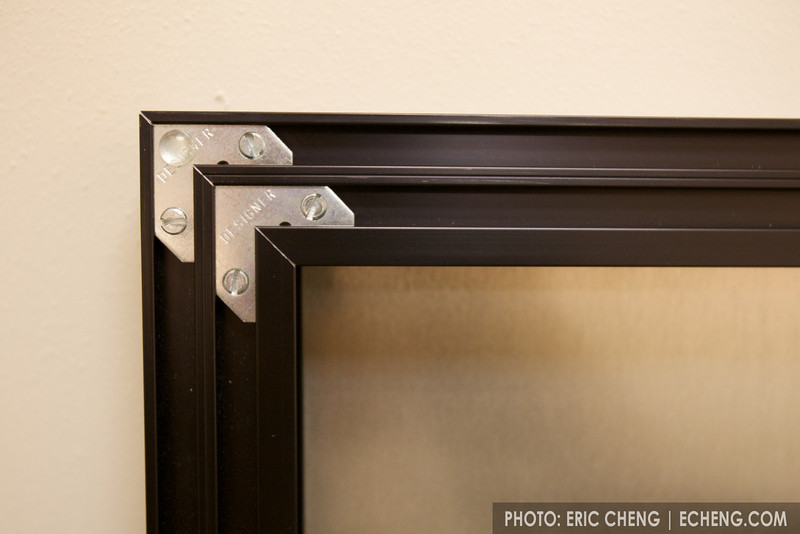 The aluminum prints are attached to a double frame, and include little rubber buttons so they don't scratch the wall.