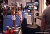 Models watch themselves being showered by Jelly Bellies at the Olympus booth