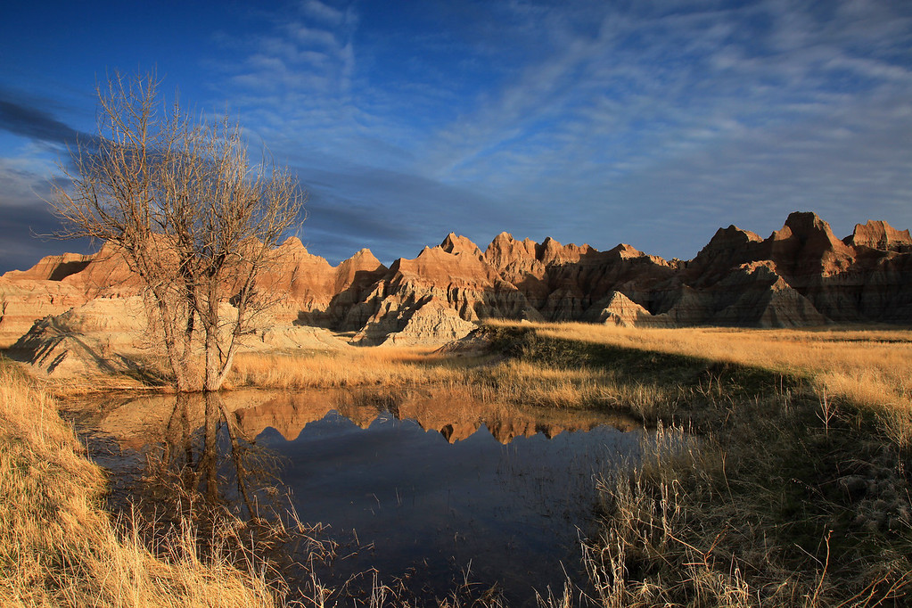 "MONDAY, APRIL 20, 2009<br /> <br /> SOUTH DAKOTA 0871<br /> <br /> ""Spring Sunrise, Badlands National Park""<br /> <br /> I have been to the Badlands in South Dakota a few times now, and with each visit I enjoy the area even more. My previous trips were just quick ""through-visits"" on my way home from other travels out west. This time, however, I was able to spend almost two full days in the area. I arrived in Badlands National Park after spending the day traveling through the Pine Ridge Reservation and visiting Wounded Knee. The whole area is beautiful and I can only imagine what it must look like in the summer, when things are a little 'greener'. The grasses everywhere were still quite brown, nothing had really greened up yet. <br /> <br /> As I arrived in the Badlands I started noticing a lot of standing water in the low-lying areas along the side of the road, and some patches of snow here and there. When I got to the park's visitor center the staff informed me that they had quite a bit of moisture in the past couple of weeks, in the form of both rain and snow. Consequently, there were lots of puddles and in some places larger pools of water. In the larger pools, choruses of frogs were croaking and singing to their heart's content. These pockets of water really made the visit interesting for photographs, as I was able to make several exposures of the hills of the badlands reflected in these pools of water. <br /> <br /> While making the image above, about half an hour after sunset, a car pulled up alongside mine on the side of the road. A voice came from the window... ""Great spot, huh?"" I turned and voiced my agreement, then got up (I had been sitting on the ground with my tripod set low to get the above shot) and walked over to the car to chat some more. The friendly voice in the car belonged to Carl Johnson, who is currently the artist-in-residence at Badlands National Park. As it turned out, he's a photographer, too. He lives in Anchorage, Alaska but explained that he was a guide for a while in the Boundary Waters, up the Gunflint Trail. I said ""No kidding... I'm from Grand Portage."" To which he responded ""I used to work as a security guard in the Grand Portage Casino during the winter, in between my summer guiding job."" What a small world! It turns out he worked at the casino back when I was managing the marina in Grand Portage. At any rate, we had a nice visit and we swapped website information. If you'd like to visit Carl's site, go to <a href=""http://www.carljohnsonphoto.com/"">http://www.carljohnsonphoto.com/</a> and if you'd like to see his work from the Badlands, click on the ""Blog"" link at the top of his main website page. He has some nice work, and its worth a bit of your time to visit his site. <br /> <br /> Tomorrow, I head for home. The Badlands marks the last of my ""tourist"" stops for this trip. I am staying in Duluth tomorrow night, and tuesday night I am scheduled to give a slide show and a talk about my trip and my photography in general to the Duluth-Superior Camera Club. Hopefully they will like what I have to share!<br /> <br /> Camera: Canon EOS 5D Mark II<br /> Lens: Canon EF 24-105mm<br /> Focal length: 24mm<br /> Shutter speed: 1/20<br /> Aperture: f/16<br /> ISO: 100"