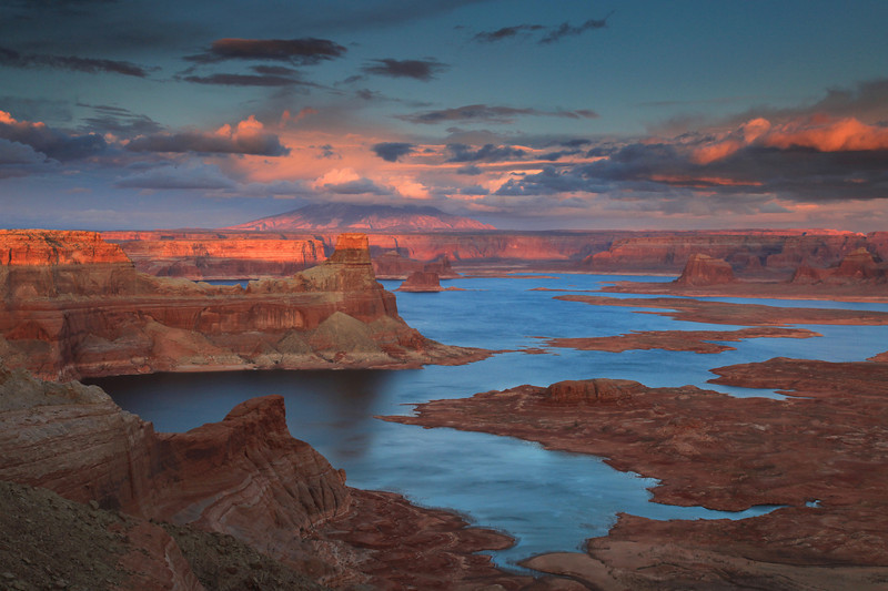 "SATURDAY, APRIL 11, 2009<br /> <br /> UTAH 9834<br /> <br /> ""Sunset, Alstrom Point""<br /> <br /> I wasn't really looking forward to today, since the forecast was calling for some pretty miserable weather all day. That's just how it started out, too. I stayed in Kanab, Utah last night and when I woke this morning it was going back and forth between rain and snow. When I got in the car and decided to head towards Page, Arizona it was hailing... actually more like kind of a slush coming down. Kanab isn't a very big town, and by the time I drove from one side of town to the other my car was covered in this hail/slush mix and I had to pull over to clear my wipers of the mess. Once I got a few miles outside of town, the clouds parted and the sun came out. It was sunny and warm (65 to 70 degrees) the rest of the day!<br /> <br /> On my way out of town I stopped at the Kanab visitor center for the Grand Staircase-Escalante National Monument. I ran into a very helpful older man with a white beard who has lived in the Page/Kanab area for the past 30 years. I told him I was interested in trying to get to Alstrom Point on Lake Powell, but wasn't sure of the way since the route is off the main roads. He gave me directions on how to get there and we visited for quite a while about other areas of interest as well. Once I had my fill of local knowledge, I thanked him and headed for Page and Lake Powell.<br /> <br /> For those of you who might not know, Lake Powell is a man-made lake, created from the construction of the Glen Canyon dam in Page, Arizona. The dam is in Arizona, but the majority of the lake lies in Utah. Lake Powell and the surrounding land makes up what is known as the Glen Canyon National Recreation Area. There are a couple of marinas on the lake, and houseboating is big business there. If you drive near the main marina you can see row after row of houseboats.<br /> <br /> I spent a good part of the day just exploring the part of the lake that is right near Page. It certainly is a beautiful area... I could easily see myself living here. I wanted to shoot the sunset from Alstrom Point, and based on my ""local knowledge"", when 5:30 rolled around I figured I better get started on those backroads to get to the point. My directions told me it was about 25 miles to the point, which turned out to be spot-on. My GPS read 25.2 miles once I got there. I was told the way would be ""relatively"" easy so long as the clay portion of the road was dry. And it was, for the most part. There was only one section about 100 feet long that was a little bit wet but my Honda Element made it through without any problem, although not before flinging up a decent amount of mud and getting my car good and dirty.<br /> <br /> Alstrom Point was sublime. I chose to walk the last mile and a half of ""road"" which went right out onto the point itself. I could have driven it, but it was easier to walk. The road at that point was more suited for a high-clearance Jeep. The sunset turned out to be the best one of the trip so far. The rocks seemed to glow as the light hit them, and the clouds were vibrant hues of pink and blue. After this amazing light show was over, I ate my Subway sandwich that I had brought along for supper, then opened the rear hatch on my car and rolled my sleeping bag out on the floor. I camped in the car for the night, since I didn't feel like driving back out on that road in the dark. It was a wonderful night and it was warm enough that I left the hatch open while I slept (no bugs here.... yay!!!!!), with the warm Arizona breeze keeping me company all night long.<br /> <br /> Camera: Canon EOS 5D Mark II<br /> Lens: Canon EF 24-105mm<br /> Focal length: 47mm<br /> Shutter speed: 1/13<br /> Aperture: f/16<br /> ISO: 400"