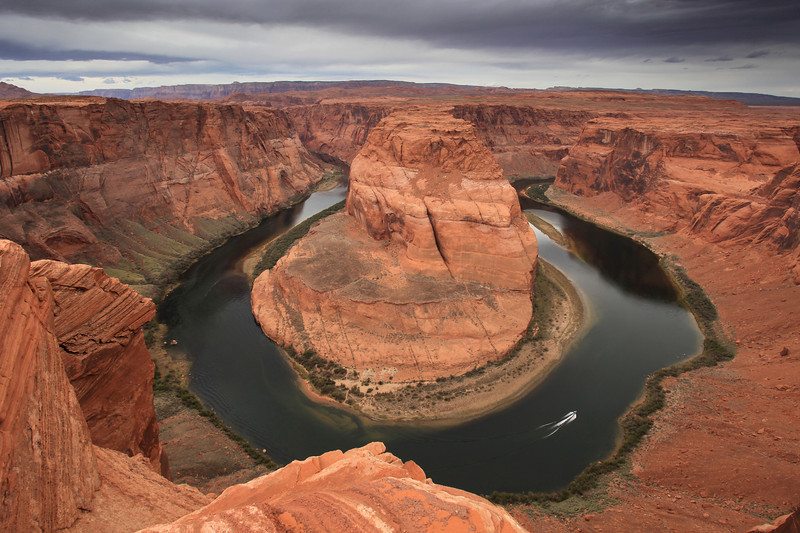 "TUESDAY, APRIL 14, 2009<br /> <br /> ARIZONA 0152<br /> <br /> ""Horseshoe Bend""<br /> <br /> My timing was a little bit off today. Apparently I just missed, by a matter of minutes, the opportunity to photograph a California Condor perched on the edge of the gorge at Horseshoe Bend. As I walked the trail to the edge of the gorge, I met another photographer who was heading back to his car. He noticed I was carrying a tripod and he stopped to tell me about the condor. He said there was a condor that had been sitting on a rock right on the edge of the gorge for close to half an hour. He pulled out his camera and showed me the images that he had just taken. They were unbelievable. Condors aren't exactly the prettiest birds, but they are big and very rare. This guy had some great shots of the bird, but did not have a website to share where the shots could be seen.<br /> <br /> I may have missed the chance to photograph the unique bird, but I still had a great time at Horseshoe Bend. The bend is just a few miles south of Page, Arizona on the Colorado River. It is very easy to get to via a relatively short (although sandy) trail from the highway. During my visit there were about 50 other people there at the same time. The little parking lot at the trailhead was almost full, and included one tour bus, which apparently was filled with French people. Which brings me to one oddity of this trip... at times it seems as though I have heard more French than English being spoken as I visit some of these areas in the southwest. Today I felt like I was back in France as the people from the tour bus were spread out along the trail and I could hear French being spoken almost the whole time I was at Horseshoe Bend. I guess the southwest has become quite popular with European travelers!<br /> <br /> Camera: Canon EOS 5D Mark II<br /> Lens: Canon EF 17-40mm<br /> Focal length: 17mm<br /> Shutter speed: 1/40<br /> Aperture: f/16<br /> ISO: 100"