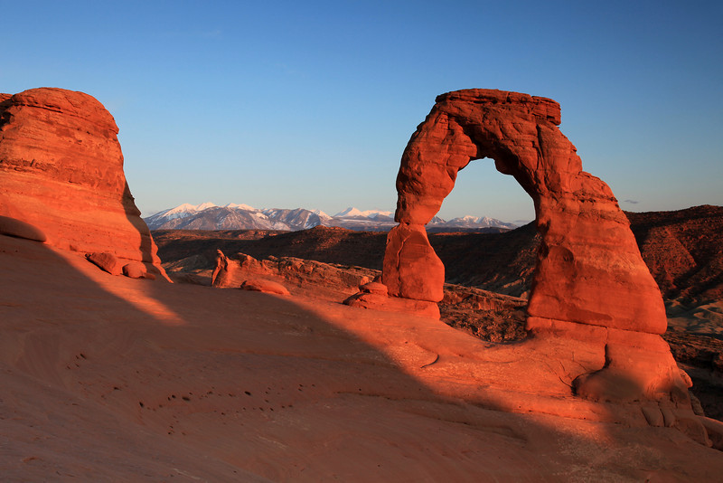 "FRIDAY, APRIL 17, 2009<br /> <br /> UTAH 0629<br /> <br /> ""Sunset, Delicate Arch""<br /> <br /> Ah, Arches.... what was supposed to be a main focus of this trip ended up being just a short visit. I was originally planning on visiting Arches FIRST on this trip, and spending a few days there. Plans changed when I found out that Moab was hosting the ""Easter Jeep Safari"". I like to avoid crowds, so I changed my plan and decided to hit Arches and Moab on the tail end of my trip, after the madness of the Jeep Safari had departed. I stayed in Moab for two nights, and spent only half of my time in Arches... the other half in Canyonlands. <br /> <br /> I was discouraged when, on Thursday morning at about 10:00, I arrived at the park entrance only to find a long line of about 40 cars waiting to get into the park. Eventually I made it in, only to find that parking at almost every trailhead was non-existent... all the spots were already taken, with overflow spilling down both sides of the road in both directions. There was one thing that I knew I had to do, though... and that was hike to Delicate Arch, easily the most famous arch in the park. I wasn't going to do that in the middle of the day, so I left the park for a while and came back to hike to the arch at sunset.<br /> <br /> When I arrived at Delicate Arch there weren't any clouds to make a nice photogenic sky, but the arch was bathed in a beautiful glow from the setting sun. There were about 25 other people already there, most of them just enjoying the view, but a few were taking pictures. One thing is for certain, its practically impossible to enjoy the golden hour at Delicate Arch by yourself. Its just too popular. However, I found that if you wait 10 minutes after the sun goes down, everyone is gone! I stayed for about an hour after sunset, debating whether or not to hang around and make some star trail images of the arch. I decided against that when some clouds started to roll in from the east. So, I headed back to the car. I had my headlamp with me, but thinking about the words of Edward Abbey which I had read the night before, I chose not to use it. I still had enough light to see by anyway.<br /> <br /> Edward Abbey wrote in his book ""Desert Solitaire"", which is about his time as a ranger at Arches National Park, before it was ""discovered"":<br /> <br /> ""There's another disadvantage to the use of the flashlight: like many other mechanical gadgets it tends to separate a man from the world around him. If I switch it on my eyes adapt to it and I can see only the small pool of light which it makes in front of me; I am isolated. Leaving the flashlight in my pocket where it belongs, I remain a part of the environment I walk through and my vision though limited has no sharp or definite boundary.""<br /> <br /> I realized this long ago, which is why my headlamp is only used when absolutely necessary. And tonight, it was not absolutely necessary.<br /> <br /> Arches is a very popular park these days... and I couldn't help but wonder as I fought the crowds what it would have been like to visit the park during the early days, when Abbey was a ranger here and the park had no paved roads and no crowds. I struggle with the ""busy-ness"" of some parks. I do like that most people, regardless of their ability, are able to visit some of these natural treasures. However, it is this idea of easy access that also works to strip away some of the sense of appreciation that people have for these areas. If they don't have to work hard to see it, they won't appreciate it as much. To quote the newsletter from Arches National Park: ""Can't decide what to do? Well, forget the schedule and stay another day. If you try to see too much on your vacation, you end up really 'seeing' nothing.""<br /> <br /> Camera: Canon EOS 5D Mark II<br /> Lens: Canon EF 24-105mm<br /> Focal length: 40mm<br /> Shutter speed: 1/5<br /> Aperture: f/16<br /> ISO: 100"