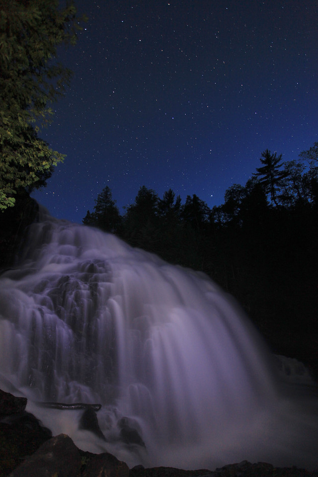 "MONDAY, AUGUST 24, 2009<br /> <br /> PIGEON RIVER 4935<br /> <br /> ""Night comes to Partridge Falls""<br /> <br /> I am really having a lot of fun with my Canon 5D Mark II. This camera is allowing me to capture images that I never thought were possible. It certainly is a wonderful camera for night photography! The waterfall seen here is Partridge Falls on the Pigeon River in northeast Minnesota. This river is the border between the U.S. and Canada in this part of the state. My friend Roger was up for the weekend and when Roger visits we usually try to do a session of night photography. The concept portrayed in this image was actually Roger's idea. I was in between shooting images when all of a sudden Roger walked out in front of me and stood near the base of the falls, using his flashlight to paint light up, down, left and right across the falls. After I saw his image I knew I had to try one of my own. I have always wanted to try shooting Partridge Falls with the stars above it but with the cameras I used to have the results, while interesting to view at web size, would have been too noisy for printing. The Canon 5D Mark II changes that. I have already had a print of one of these images made, and it is stunning! <br /> <br /> Camera: Canon EOS 5D Mark II<br /> Lens: Canon EF 17-40mm<br /> Focal length: 17mm<br /> Shutter speed: 30 seconds<br /> Aperture: f/4<br /> ISO: 1000"