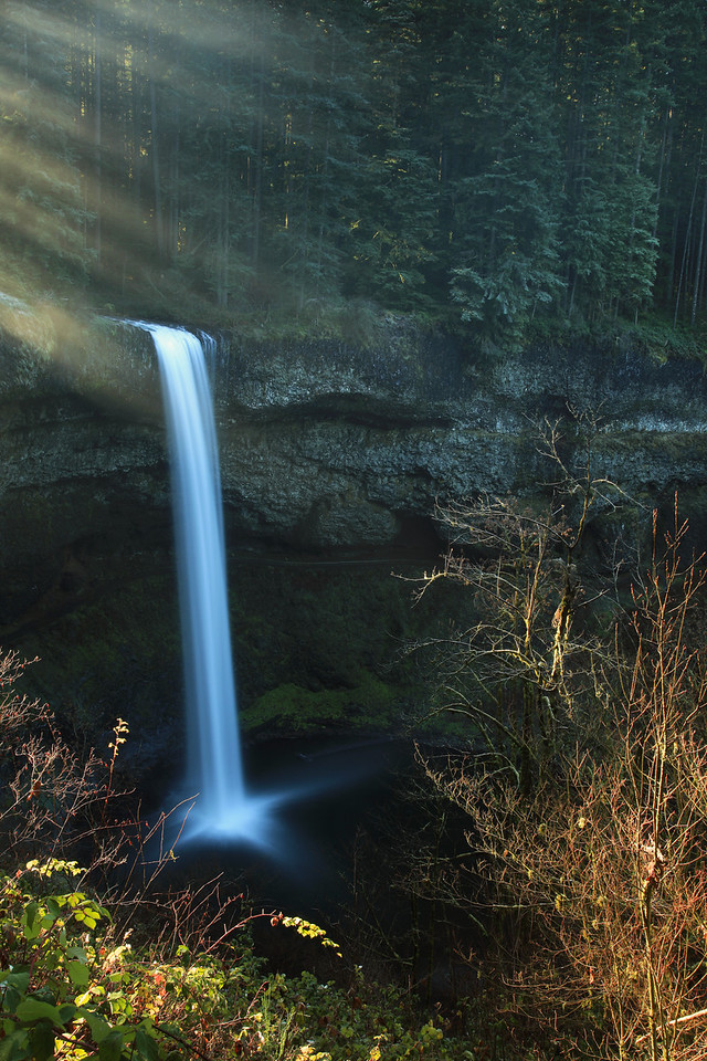 "SATURDAY, DECEMBER 5, 2009<br /> <br /> OREGON 1576<br /> <br /> ""Morning rays at South Falls""<br /> <br /> The only thing on today's agenda was a visit to Silver Falls State Park, in my opinion one of the jewels of Oregon. Silver Falls is an amazing park and is Oregon's largest state park. The main park attraction is the ""Trail of Ten Falls"", a hiking trail which passes... you guessed it: ten waterfalls! And, five of them are over 100 feet tall! Pictured here is South Falls, possibly the most popular waterfall within the park. South Falls drops a total of 177 feet. <br /> <br /> Camera: Canon EOS 5D Mark II<br /> Lens: Canon EF 24-105mm<br /> Focal length: 32mm<br /> Shutter speed: 6 seconds<br /> Aperture: f/16<br /> ISO: 50"