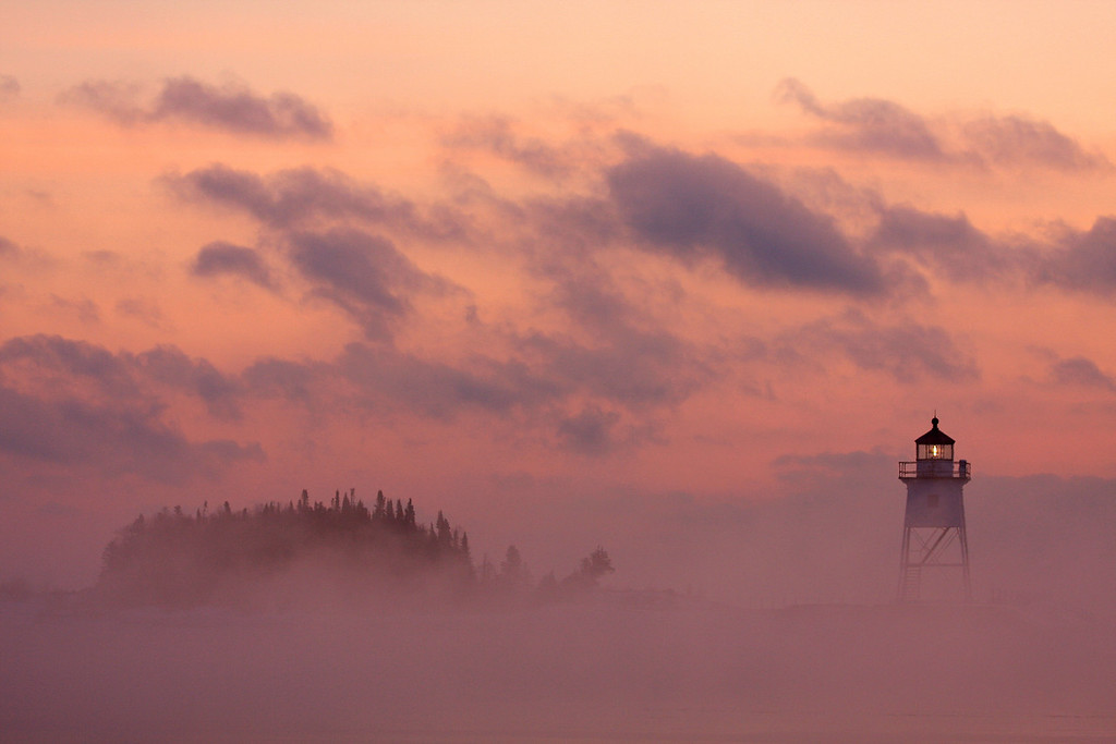 "SUNDAY, FEBRUARY 1, 2009<br /> <br /> SUPERIOR WINTER 4937<br /> <br /> ""Sea smoke at sunrise, Grand Marais Lighthouse""<br /> <br /> I heard through the ""photo grapevine"" that some big waves had produced some HUGE piles of ice at Stoney Point between Duluth and Two Harbors. So, yesterday I woke early to drive down and photograph the ice piles. I timed it so I would be in Grand Marais for sunrise, which turned out to be a very good plan. I arrived in Grand Marais about 15 minutes before the sun was to come up, and there was sea smoke (steam) drifting in and out of the harbor. There was also a large cloud bank on the horizon, which meant that it took a while for the sun to actually come up. This didn't hurt the images I made, however. The sky had a beautiful pink glow that easily made this one of the best sunrises I've ever photographed on the lake. <br /> <br /> Camera: Canon EOS 40D<br /> Lens: Canon EF-S 100-400mm<br /> Focal length: 120mm<br /> Shutter speed: 1/160<br /> Aperture: f/5<br /> ISO: 200"