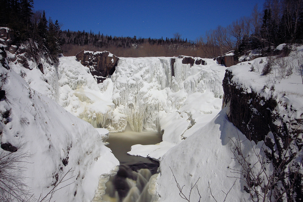 "FRIDAY, JANUARY 9, 2009<br /> <br /> PIGEON RIVER 4394<br /> <br /> ""Moonlight on a frozen High Falls - Grand Portage State Park, MN""<br /> <br /> As is my habit each month, when the moon is full I try to get out for at least one night of shooting in the moonlight. So it was that friday evening found my dad and I snowshoeing to High Falls on the Pigeon River at 9:00 at night. The ""official"" full moon is not until Sunday night, but it sure seemed full tonight. With all the snow that we've had combined with crystal clear skies, there was lots of reflected light from the moon, making night exposures easy. I was able to pull off 15 second exposures where normally in the non-winter months I have to run exposures of 30 to 40 seconds to get enough light in the shot. Anyway, it was a great night and it was fun spending time with my dad snowshoeing in the moonlight. <br /> <br /> Camera: Canon EOS 40D<br /> Lens: Canon EF-S 10-22mm<br /> Focal length: 22mm<br /> Shutter speed: 30 seconds<br /> Aperture: f/4.5<br /> ISO: 500"