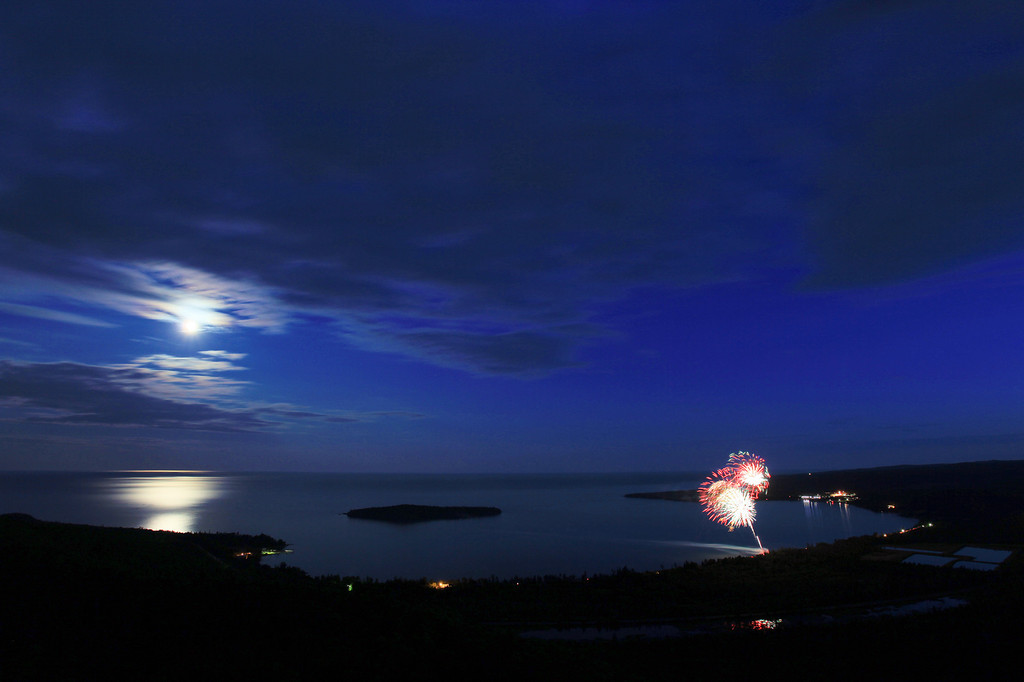 "SUNDAY, JULY 5, 2009<br /> <br /> FIREWORKS 3262<br /> <br /> ""Fireworks and moonlight over Grand Portage Bay - July 4, 2009""<br /> <br /> For years I've been wanting to watch the Grand Portage fireworks from the summit of Mt. Josephine. This year, I finally had a kindred spirit who had the same desire... my friend Roger ( <a href=""http://www.rogernordstromphoto.com"">http://www.rogernordstromphoto.com</a>). Roger and I hatched a plan to hike up to the summit in time to catch the sunset then wait until the fireworks started and photograph them as well. We both figured that it might provide for a cool vantage point to view the fireworks, and boy were we right! It was interesting to be looking down on the fireworks show rather than craning our necks skyward.<br /> <br /> After the show was over, we were treated to a couple of hours of very nice moonlight over Grand Portage Bay and Lake Superior. We sat on the rocks high above the bay and watched as the moonlight shimmered and danced on the waters of the lake. After a while we figured we better get some sleep, since we were planning on shooting sunrise from the summit as well. So, we pulled out our sleeping bags and each found a spot on the rocks that wasn't too rough on our backs, then slept under the stars. <br /> <br /> Camera: Canon EOS 5D Mark II<br /> Lens: Canon EF 17-40mm<br /> Focal length: 17mm<br /> Shutter speed: 30 seconds<br /> Aperture: f/8<br /> ISO: 200"