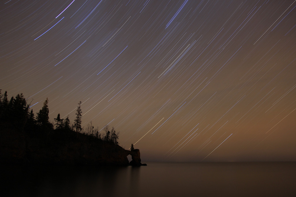 "WEDNESDAY, NOVEMBER 11, 2009<br /> <br /> STAR TRAILS 9521<br /> <br /> ""Star trails over the Tettegouche Arch""<br /> <br /> After watching the light for a while I met up with a friend of mine and together we decided to head up to Tettegouche State Park and try shooting some star trails over the rock arch that is on the Tettegouche shoreline of Lake Superior. We spent a couple of hours shooting a fantastic night sky over the arch. It was an incredible night to be outside!   There was no wind and the lake was as flat as a pancake. <br /> <br /> Camera: Canon EOS 5D Mark II<br /> Lens: Canon EF 24-105mm<br /> Focal length: 24mm<br /> Shutter speed: 53 minutes<br /> Aperture: f/4<br /> ISO: 100"