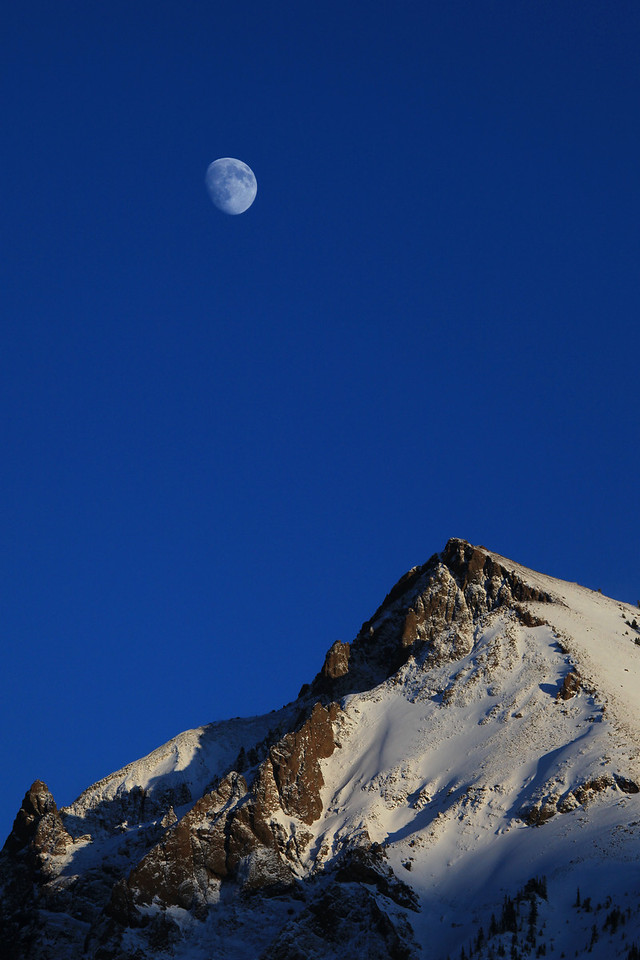 "SUNDAY, NOVEMBER 29, 2009<br /> <br /> MONTANA 0670<br /> <br /> ""Mountain Moon""<br /> <br /> This picture of the moon off the top of a mountain peak was taken just outside of Cooke City, Montana.<br /> <br /> Camera: Canon EOS 5D Mark II<br /> Lens: Canon EF 100-400mm<br /> Focal length: 220mm<br /> Shutter speed: 1/800<br /> Aperture: f/10<br /> ISO: 400"