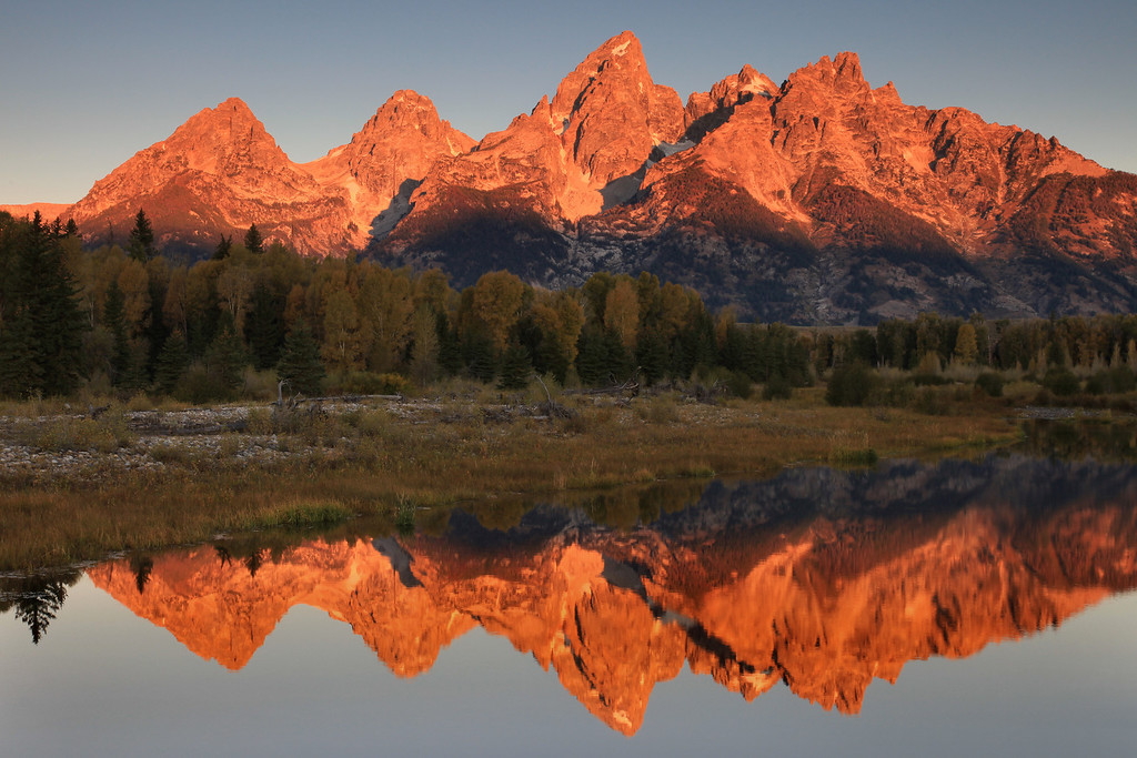 "WEDNESDAY, SEPTEMBER 23, 2009<br /> <br /> WYOMING 7154<br /> <br /> ""First light on the Tetons""<br /> <br /> After spending a full day, sunrise to sunset, in Yellowstone yesterday, we drove to Teton Village just outside of Jackson, Wyoming where we would be spending the next couple of nights. We got in pretty late, but that didn't stop us from getting up early and heading out to shoot the sunrise. Today's plan was to shoot sunrise at Schwabacher's Landing, one of the iconic photo locations in Grand Teton National Park. Schwabacher's Landing overlooks the Teton Range, with a very photogenic beaver pond in the foreground. <br /> <br /> Upon our arrival at Schwabacher's Landing, we saw right away that we certainly weren't going to have the place to ourselves (if that's even possible!). The parking area was already full of vehicles, and we saw what looked to be about 30 photographers already set up along the first couple of bends in the trail. We squeezed our way in between the other photographers and waited for the sun to hit the peaks. After only a few more minutes the tops of the peaks started to glow as the sunlight washed down them from top to bottom. All of a sudden the silence was broken by the sound of dozens of camera shutters clicking one after the other.<br /> <br /> Once the sunlight had worked its way to the base of the mountains I started working my way upstream, finding myself stopping again after only traveling a few steps, having seen another composition catch my eye. The going was slow in this special place, as each bend in the trail presented a whole new batch of photo opportunities.<br /> <br /> Part-way up the trail I actually ran into someone I know from back home... Don, who owns the camera store in Duluth. He and his wife were there with some friends. I snuck up alongside Don and exhaled rather heavily, then said ""Well.... its not Lake Superior, but I guess it'll do!"" Don started to mutter a reply, then turned and saw that it was me. ""Hey! How are you?"" It was a priceless moment :-)<br /> <br /> Camera: Canon EOS 5D Mark II<br /> Lens: Canon EF 24-105mm<br /> Focal length: 55mm<br /> Shutter speed: 1/5<br /> Aperture: f/16<br /> ISO: 100"
