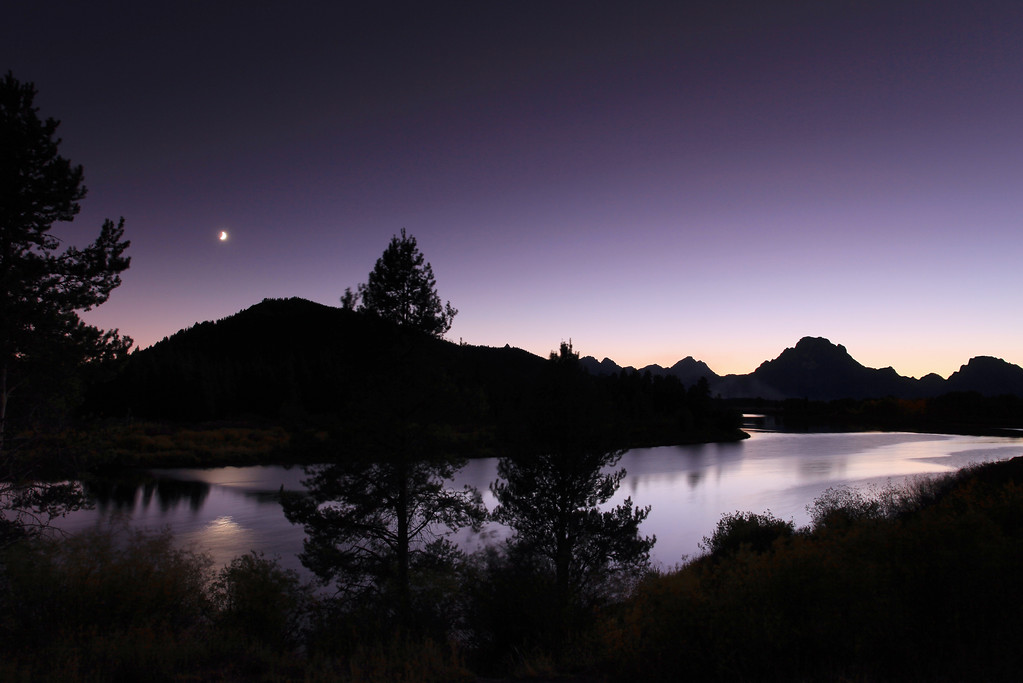 "WEDNESDAY, SEPTEMBER 23, 2009<br /> <br /> WYOMING 7322<br /> <br /> ""Moon over Oxbow Bend""<br /> <br /> We were pretty tired after our long day in Yellowstone and our early morning of shooting the Teton Mountains, so we decided to take it easy in the afternoon and just spend some time relaxing in our suite back at the hotel. Which, by the way, was really an incredible place. If you are planning on visiting the Tetons and looking for a REALLY NICE place to stay, check out Hotel Terra  <a href=""http://www.hotelterrajacksonhole.com/"">http://www.hotelterrajacksonhole.com/</a>). Its pricey, but if you have a couple of friends to split the cost with, its not so bad.<br /> <br /> After getting some rest, we headed back out for sunset. We decided to try Oxbow Bend, another popular place... a bit too popular, as it turns out. When we arrived at Oxbow Bend the parking area was full and the cars were lined up on the sides of the road for quite a ways in both directions. The area was crawling with people, so we just drove past and turned on the next road we came to, which was a gravel road on the left. This road went for a little over a mile and ended up at the Snake River, just upstream from Oxbow Bend. We walked around a little bit, and just decided to head back to Oxbow Bend after the crowds were gone. Our focus this evening was going to be shooting the night sky and the stars.<br /> <br /> We waited until about half an hour after sunset then headed back to Oxbow Bend. Almost all of the cars were gone; only a few remained. We had enough light to make some really nice exposures of the river with Mt. Moran in the distance. An added bonus was the moon, which provided some extra drama to some of the shots.<br /> <br /> Camera: Canon EOS 5D Mark II<br /> Lens: Canon EF 17-40mm<br /> Focal length: 22mm<br /> Shutter speed: 15 seconds<br /> Aperture: f/10<br /> ISO: 200"