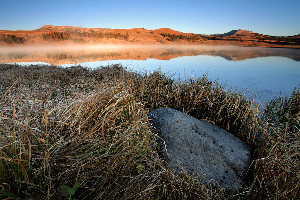 "TUESDAY, SEPTEMBER 22, 2009<br /> <br /> WYOMING 6679<br /> <br /> ""Sunrise on Swan Lake""<br /> <br /> Tuesday morning greeted us with bitter cold temperatures... I'm not sure what the temp actually was, but it felt like it was around 20 to 25 degrees. There wasn't a lick of wind, though, and its always good NOT to have wind when its cold! Jake and Stuart already had our sunrise location picked out, which was on a lovely little body of water known as Swan Lake. As we made the drive to Swan Lake, we passed several geothermal areas that were throwing up quite a bit of steam in the cold morning air. It was rather surreal to see all this steam drifting skyward as we passed the geothermal areas... it felt like we were on a different planet. <br /> <br /> Camera: Canon EOS 5D Mark II<br /> Lens: Canon EF 17-40mm<br /> Focal length: 17mm<br /> Shutter speed: 0.5 sec<br /> Aperture: f/16<br /> ISO: 50"