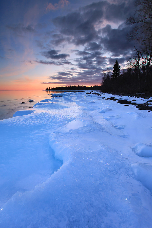 "FRIDAY, FEBRUARY 26, 2010<br /> <br /> SUPERIOR WINTER 5813<br /> <br /> ""February sunset over shore ice""<br /> <br /> Late winter is one of my favorite times of the year. I always look forward to late February and early March with great anticipation. The reason for this is simple. I love ice. As March approaches, ice buildup on Lake Superior usually increases. This was true again this year, but not to the extent that I was hoping. We had very little ice coverage on the lake in February this year mostly due to above average temperatures. It simply wasn't getting cold enough for ice to form the way it usually does. We did, however, still have plenty of ice right along the shoreline. <br /> <br /> Camera: Canon EOS 5D Mark II<br /> Lens: Canon EF 17-40mm<br /> Focal length: 17mm<br /> Shutter speed: 1/5 sec<br /> Aperture: f/16<br /> ISO: 100"