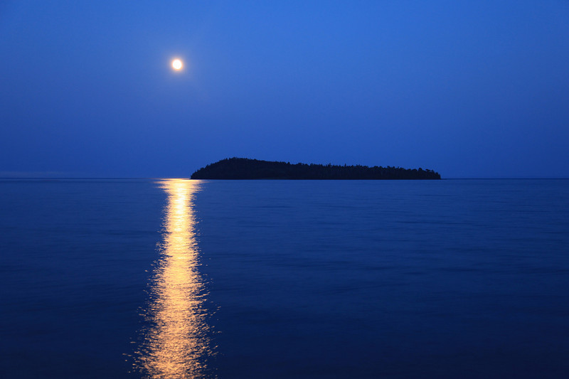 "MONDAY, JULY 26, 2010<br /> <br /> MOONLIGHT 8408<br /> <br /> ""July moon over Pete's Island""<br /> <br /> The moon over Grand Portage Bay last night was incredible. The image you see here was captured not long after sunset, after the last of the sunset color has faded from the sky and all that is left is the blue glow of dusk. I love shooting the moon when its low in the sky, as you can usually capture an incredible reflection of the moonlight on the water. I hope you all had a chance to see the moon last night. If not, well… it will be out again tonight!<br /> <br /> Camera: Canon EOS 5D Mark II<br /> Lens: Canon EF 24-105mm<br /> Focal length: 50mm<br /> Shutter speed: 2 seconds<br /> Aperture: f/4<br /> ISO: 400"
