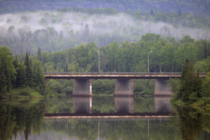 "FRIDAY, JUNE 18, 2010<br /> <br /> PIGEON RIVER 0097<br /> <br /> ""Border Bridge""<br /> <br /> The international bridge between the U.S. and Canada over the Pigeon River in Grand Portage, MN. I made this image right after it stopped raining today. The bridge's reflection on the water and the fog in the background really caught my eye. <br /> <br /> Camera: Canon EOS 5D Mark II<br /> Lens: Canon EF 100-400mm<br /> Focal length: 210mm<br /> Shutter speed: 1/250<br /> Aperture: f/5.6<br /> ISO: 400"