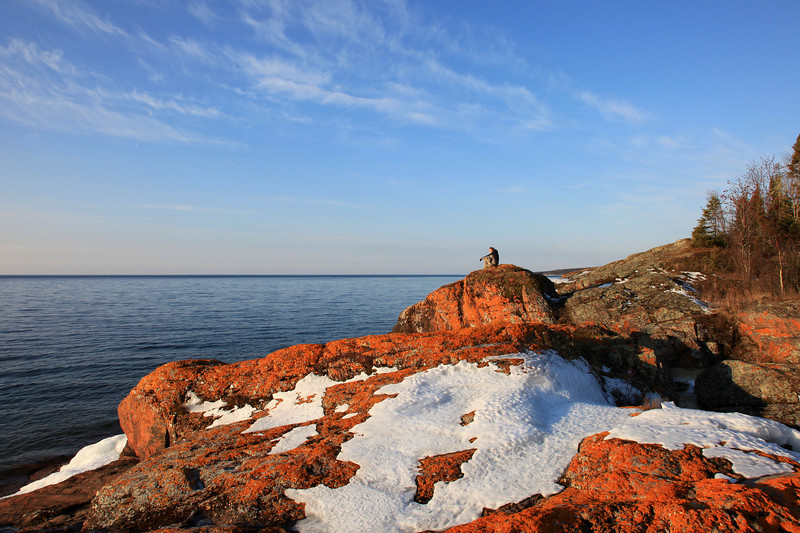 "MONDAY, MARCH 8, 2010<br /> <br /> SUPERIOR SPRING 6094<br /> <br /> ""A Superior View""<br /> <br /> After the best of the morning light was gone, we walked out to the end of Red Rock Point and just did some exploring. Almost all of the ice was gone from the point; only a few small patches remained. At one point while walking around on the point I looked up and saw Roger sitting on the rocks, enjoying the view of the lake. I couldn't resist making this image of him enjoying the view. <br /> <br /> Camera: Canon EOS 5D Mark II<br /> Lens: Canon EF 24-105mm<br /> Focal length: 24mm<br /> Shutter speed: 1/100<br /> Aperture: f/16<br /> ISO: 200"