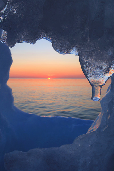 "MONDAY, MARCH 8, 2010<br /> <br /> SUPERIOR WINTER 6040<br /> <br /> ""Icy Dawn""<br /> <br /> We were exploring Red Rock Beach looking for some cool ice formations to photograph at sunrise and were about to give up when I found this small hole in the ice along the shoreline. This little ""ice window"" was only about a foot to a foot and a half tall, and I spotted it with just enough time to scramble down to it and get a shot of the sun just as it was beginning to poke up over the horizon. <br /> <br /> Camera: Canon EOS 5D Mark II<br /> Lens: Canon EF 17-40mm<br /> Focal length: 32mm<br /> Shutter speed: 1/30<br /> Aperture: f/16<br /> ISO: 200"