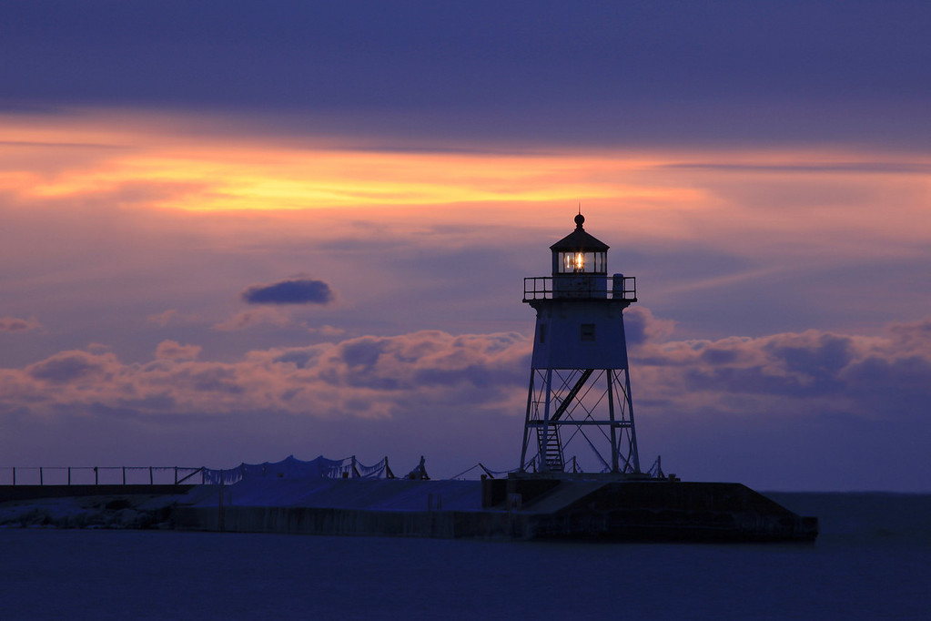 "SATURDAY, DECEMBER 10, 2011<br /> <br /> GRAND MARAIS 6914<br /> <br /> ""December Dawn over the Grand Marais Lighthouse""<br /> <br /> I went out this morning with the hopes of capturing the Lunar eclipse, but heavy cloud cover put a stop to that plan. There was, however, a small break in the clouds to the East where the sun was soon to rise. This photo was made about half an hour before sunrise when there was a nice, soft glow of color coming from behind the clouds. <br /> <br /> Camera: Canon EOS 5D Mark II<br /> Lens: Canon EF 100-400mm<br /> Focal length: 400mm<br /> Shutter speed: 3.2 seconds<br /> Aperture: f/16<br /> ISO: 100"