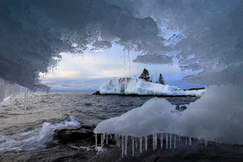 "SUNDAY, FEBRUARY 6, 2011<br /> <br /> SUPERIOR WINTER 5259<br /> <br /> ""Ice Cave at Hollow Rock""<br /> <br /> This ""window"" of ice is looking out on the little island known as ""Hollow Rock"", which has been the subject of more than a few of my previous blog entries. I feel very fortunate that I now have this image in my portfolio, since the decision to head out and shoot that morning could have easily gone the other way. We had spent 5 hours snowshoeing the previous day over some very rugged terrain, and our bodies really didn't feel like going out early in the morning and shooting again so soon after the snowshoe workout. The decision was made to head out, however, and boy am I glad that we did as several good images were made on this morning.<br /> <br /> The sunrise over Hollow Rock was very nice, with some interesting clouds to spice things up. The real treat, though, was finding two small ice caves to photograph. This particular image is of the second ice cave that I found, and when I stuck my head into this little cave I couldn't believe the view I found with Hollow Rock visible through the hole. It was as though mother nature had tailor-made this ice formation for a curious photographer to stumble upon. There wasn't much room to work inside the cave to get this image. It required crawling into the cave head-first on my stomach then propping my elbows on the rocky ground to brace the camera for this shot. There was no room at this angle to use my tripod.<br /> <br /> Camera: Canon EOS 5D Mark II<br /> Lens: Canon EF 17-40mm<br /> Focal length: 17mm<br /> Shutter speed: 1/160<br /> Aperture: f/16<br /> ISO: 200"