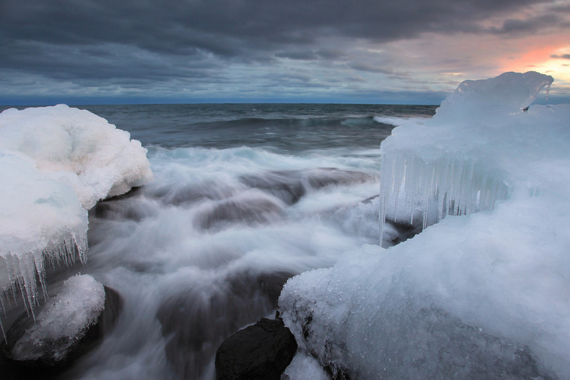 "THURSDAY, FEBRUARY 3, 2011<br /> <br /> SUPERIOR WINTER 5054<br /> <br /> ""Waves and Ice""<br /> <br /> From this evening's sunset along the Lake Superior shoreline in Grand Portage. I sacrificed warm, dry feet to get this shot :-) In order to get the angle I wanted I had to put myself in the path of the waves and as a result a couple of the larger waves washed right into this notch and the spray got my feet and legs wet almost up to my knees. By the time I was done shooting my pants were frozen stiff from the combo of water and cold air. The things us photographers do to get the images we want :-)<br /> <br /> Camera: Canon EOS 5D Mark II<br /> Lens: Canon EF 17-40mm<br /> Focal length: 17mm<br /> Shutter speed: 0.5 sec<br /> Aperture: f/16<br /> ISO: 200"
