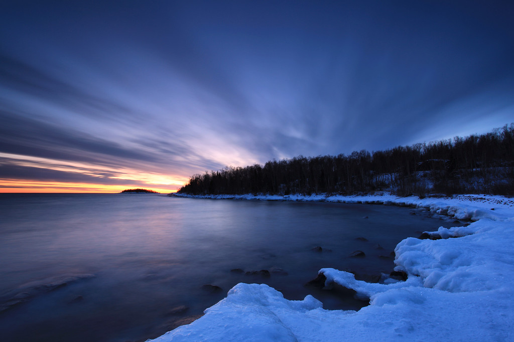 """TUESDAY, FEBRUARY 8, 2011<br /> <br /> SUPERIOR WINTER 5323<br /> <br /> """"Pancake Bay Dreamscape""""<br /> <br /> This was taken shortly after sunset today, just after the vibrant colors of sunset began to fade. This sunset easily ranks (in my book) as the most spectacular sunset so far this winter. The colors and clouds were incredible, a wonder to behold. As a photographer I am always desiring clouds like those in this image, that fan out from where the sun dipped below the horizon. Clouds like this don't seem to happen very often, but when they do it's a magical sight.<br /> <br /> Camera: Canon EOS 5D Mark II<br /> Lens: Canon EF 17-40mm<br /> Focal length: 17mm<br /> Shutter speed: 25 seconds<br /> Aperture: f/16<br /> ISO: 50"""