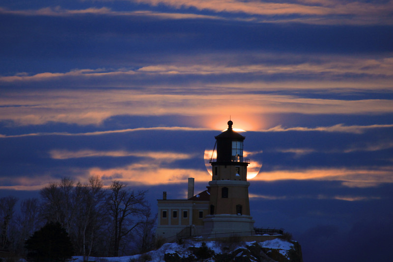 "WEDNESDAY, JANUARY 19, 2011<br /> <br /> MOONLIGHT 4580<br /> <br /> ""January Moonrise, Split Rock Lighthouse""<br /> <br /> In January it is well-known amongst photographers that the moon rises directly behind Split Rock Lighthouse on the shores of Lake Superior, and as a result several photographers make the journey every year to Split Rock to photograph this event. I don't normally do much shooting at Split Rock since it is a bit of a drive from where I live, but my friend Paul had invited me down this year to photograph the moon as it rose behind the light. We both arrived with plenty of time to spare before the moon came up, so we spent some time chatting with a few others that had gathered with us. I was the only one in our group that had never photographed the January moon over the lighthouse. <br /> <br /> Camera: Canon EOS 5D Mark II<br /> Lens: Canon EF 100-400mm<br /> Focal length: 400mm<br /> Shutter speed: 0.4 sec<br /> Aperture: f/5.6<br /> ISO: 800"