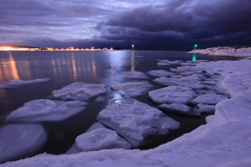 """SATURDAY, JANUARY 29, 2011<br /> <br /> MOONLIGHT 4627<br /> <br /> """"Night Storm, Grand Marais Harbor""""<br /> <br /> This image was made on my way home to Grand Portage, MN after spending the day in Duluth, MN. The drive back up the shore that night was magical. The clouds were really something, with the moonlight popping through breaks in the clouds every now and then. As I approached Grand Marais I could see that the clouds were going to be very interesting over the harbor, so I pulled in to the campground road and went down along the lake and found these nice ice cakes floating in the corner of the bay. The most amazing thing, however, was that big, dark, almost black cloud bank moving in off the lake. I spent about half an hour in this spot making images with various compositions and exposure settings, this one is my favorite of the bunch.  And yes, it was cold! The air temp wasn't too bad at 18 degrees, but the wind made it feel much, much colder. There was a fairly strong wind pushing that big cloud bank in from the lake, so the wind chill was probably below zero.<br /> <br /> Camera: Canon EOS 5D Mark II<br /> Lens: Canon EF 17-40mm<br /> Focal length: 17mm<br /> Shutter speed: 10 seconds<br /> Aperture: f/4<br /> ISO: 800"""