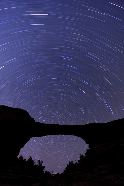 "FRIDAY, MARCH 25, 2011<br /> <br /> UTAH 8546<br /> <br /> ""Star Trails over Owachomo Bridge""<br /> <br /> As we drove towards Natural Bridges National Monument the afternoon of March 24th it looked as though the sky was not going to cooperate for shooting the stars that night. The clouds were moving in fast and soon covered most of the sky. We stuck it out, though, and are glad we did because as the sky darkened we soon started to see stars showing up through the thinning clouds. After the sun had set the clouds moved out and we ended up having a nice solid couple of hours to make star images before the clouds moved back in. I was really excited because a year ago I had been at this same location three nights in a row trying to shoot the night sky but had three nights of cloudy, uncooperative skies. This year definitely made up for last year.  I wasn't sure how this would turn out by placing the North Star directly behind the bridge, but in the end I was really happy with the result.<br /> <br /> Camera: Canon EOS 5D Mark II<br /> Lens: Canon EF 17-40mm<br /> Focal length: 17mm<br /> Shutter speed: 38 minutes<br /> Aperture: f/4<br /> ISO: 200"
