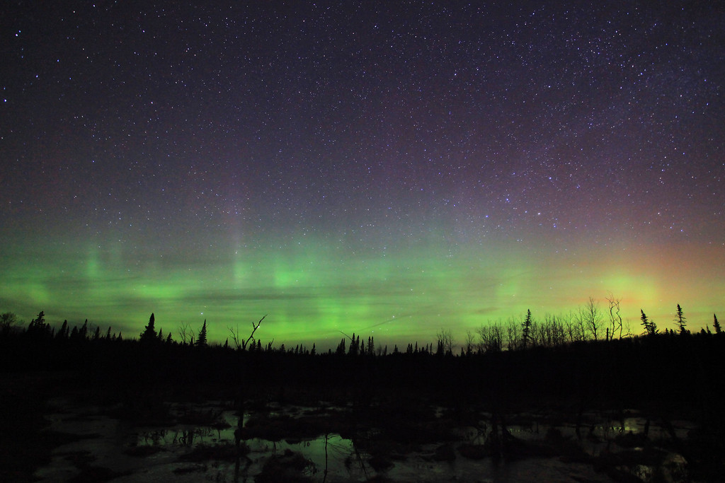 """SUNDAY, MAY 1, 2011<br /> <br /> AURORA 9935<br /> <br /> """"April Aurora""""<br /> <br /> After an hour and a half of watching, all I saw was just a faint glow in the Northern sky. I headed back home just before midnight to grab a snack, with the plan to head back out to a different location for a couple more hours. After my snack I headed back out, picking up my friend Jessica along the way. She had never seen the northern lights before, so I was really hoping they would put on a good show. We arrived at the next location about 12:30 A.M. and could still see only a very faint glow in the sky. I had two other locations I wanted to check, so we went to each of those spots and watched for a while, again seeing just a very faint glow. <br /> <br /> At 2:00 A.M. we decided to start heading back and as we were driving past one of the spots we had previously stopped at, I noticed the lights were starting to get brighter and more active. I parked the truck and we got out to watch for a bit. As soon as we got out of the truck the lights were dancing and shimmering slowly just above the horizon. Jessica was quite excited, she hadn't really expected to see a good show her first time out but indeed here it was! It's pretty cool to share someone's first experience with the Aurora. They never know quite what to think :-) One thing's for sure, they are pretty much guaranteed to be blown away by the """"cool"""" factor of this, one of nature's most amazing spectacles.<br /> <br /> Camera: Canon EOS 5D Mark II<br /> Lens: Canon EF 17-40mm<br /> Focal length: 17mm<br /> Shutter speed: 30 seconds<br /> Aperture: f/4<br /> ISO: 3200"""