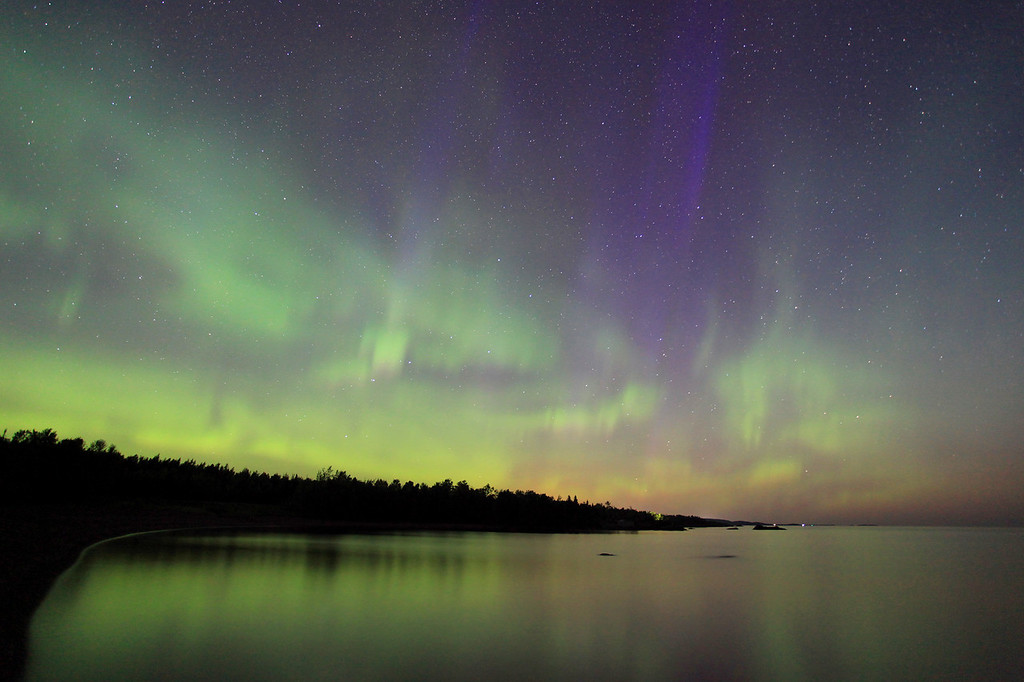 """SATURDAY, SEPTEMBER 10, 2011<br /> <br /> AURORA 2496<br /> <br /> """"Early morning Aurora over Deronda Bay""""<br /> <br /> With the knowledge of the incoming CME's, and their expected time of arrival the night of September 10th, I started making my plans. I had to work on the 10th, so I knew that without some solid sack time I would be a zombie before the lights started to flare up. So, as is my normal plan of attack when shooting the Northern lights, I got done with work on the 10th, went home and went straight to bed. I slept from 5:00 PM until 10:00 PM, and was then refreshed enough (I hoped) for a full night of shooting. <br /> <br /> As it turns out it was a good thing I got that sleep time in, because the lights didn't really start with any significance until just after midnight, and they continued all night until daylight started to creep into the sky, just before 6:00 AM. This particular photo was made at 4:42 AM along the shores of Lake Superior. Before moving to the shoreline, I had spent most of the night up on Mt. Maude, where the higher elevation provides almost a 360 degree view of the night sky. While on Mt. Maude I took a series of almost 400 photos of the dancing Northern lights and condensed them into a timelapse video, my first ever attempt at such a thing. All in all, it was a tiring, yet very rewarding, night of photography! <br /> <br /> Camera: Canon EOS 5D Mark II<br /> Lens: Canon EF 17-40mm<br /> Focal length: 17mm<br /> Shutter speed: 30 seconds<br /> Aperture: f/4<br /> ISO: 2500"""