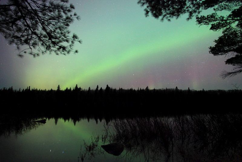 """WEDNESDAY, APRIL 25, 2012<br /> <br /> AURORA 6857<br /> <br /> """"Aurora Arc over Speckled Trout Lake""""<br /> <br /> The last few times I've gone out shooting the Aurora I've been trying to get more creative with some of my compositions.  I've been trying new locations as well as new perspectives.  The above photo is one such perspective, with the lights reflecting in the lake and the top corners of the image framed by pine branches.  I personally really like this composition.  To me it feels like I am looking through a window out into the scene beyond.<br /> <br /> Camera: Canon EOS 5D Mark II<br /> Lens: Canon EF 17-40mm<br /> Focal length: 17mm<br /> Shutter speed: 30 seconds<br /> Aperture: f/4<br /> ISO: 2500"""
