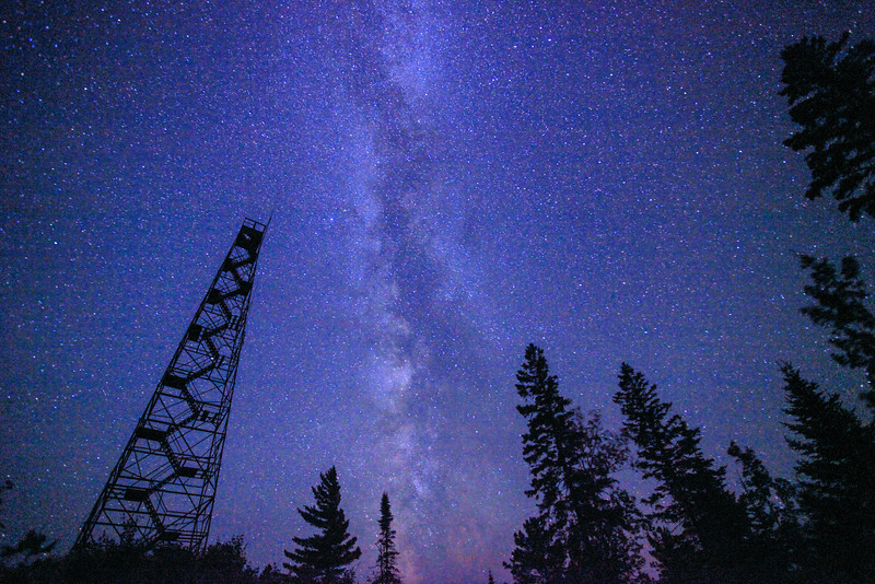 "TUESDAY, AUGUST 14, 2012<br /> <br /> MILKY WAY 9275<br /> <br /> ""Fire Tower and the Milky Way Galaxy""<br /> <br /> My favorite shot from this weekend :-) This photo was taken while we were watching the Perseid meteor shower. My camera had been set up doing a sequence of images for a timelapse video when I noticed the nice alignment of the Milky Way between the fire tower and these trees. I had to take a break from shooting the timelapse sequence in order to capture this photo before the Milky Way moved too far to the west. Sure was a beautiful night for photographing the Milky Way. <br /> <br /> Camera: Canon EOS 5D Mark II<br /> Lens: Canon EF 17-40mm<br /> Focal length: 17mm<br /> Shutter speed: 30 seconds<br /> Aperture: f/4<br /> ISO: 6400"