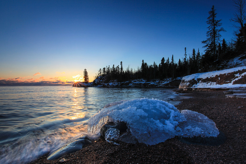"MONDAY, DECEMBER 31, 2012<br /> <br /> SUPERIOR WINTER 8655<br /> <br /> ""Last Sunrise of 2012""<br /> <br /> Last sunrise of 2012 in Grand Portage on the Lake Superior shoreline.  I had to scramble to get to this spot, mostly because I didn't give myself enough time to get there to scope it out before the sun rose.  Luckily, I am quite familiar with this shoreline and know that there are some nice rocks there.  What I wasn't expecting was this really neat cap of ice covering this rock, with icicles hanging down on the side facing the lake.  It made for a really nice foreground.<br /> <br /> I hope everyone has a wonderful, fun (and safe!) time ringing in the new year! <br /> <br /> Camera: Canon EOS 5D Mark II<br /> Lens: Canon EF 17-40mm<br /> Focal length: 17mm<br /> Shutter speed: 1/5<br /> Aperture: f/22<br /> ISO: 100"