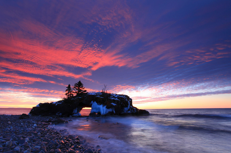 "SUNDAY, FEBRUARY 5, 2012<br /> <br /> SUPERIOR WINTER 4782<br /> <br /> ""February Sunrise over Hollow Rock""<br /> <br /> Due to a variety of reasons I have not been getting out and doing much shooting this winter, mostly because the winter conditions just have not been very favorable.  A very mild winter with very little snowfall and almost no ice production on Lake Superior has meant that the things I normally love to photograph this time of year are simply nonexistent.  This weekend, however, my friend Roger  <a href=""http://www.rogernordstromphoto.com/"">http://www.rogernordstromphoto.com/</a>) was up for a visit so of course we got out and did some shooting.  It's a good thing we did, too, as yesterday morning we witnessed what had to be one of the best winter sunrises I've ever seen.  The high-altitude clouds were incredible and did a great job of reflecting the light from the sun as it rose above the horizon.  This morning's sunrise was beautiful as well, but lacked any clouds to add interest to the sky.<br /> <br /> Camera: Canon EOS 5D Mark II<br /> Lens: Canon EF 17-40mm<br /> Focal length: 17mm<br /> Shutter speed: 2 seconds<br /> Aperture: f/16<br /> ISO: 100"