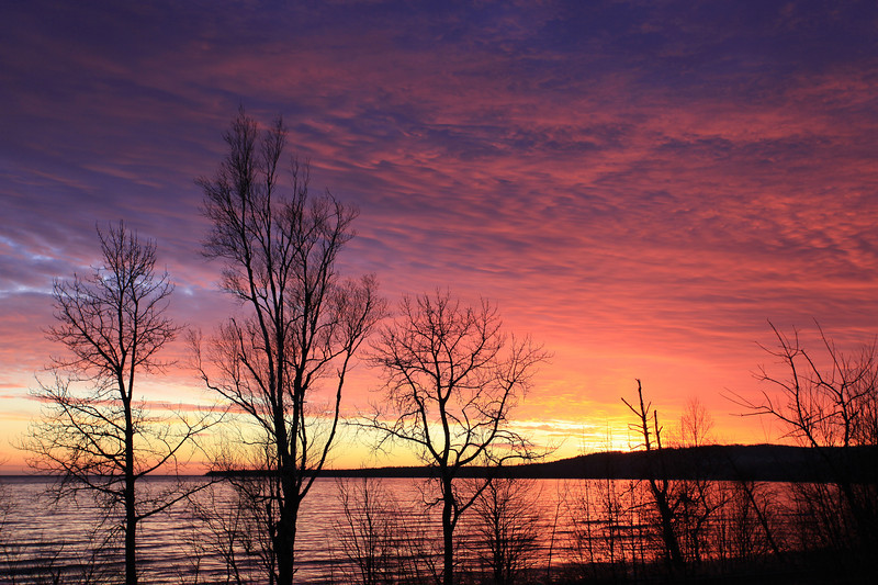 "TUESDAY, JANUARY 10, 2012<br /> <br /> SUPERIOR WINTER 4587<br /> <br /> ""Sunset on the bay""<br /> <br /> Grand Portage Bay on Lake Superior - Grand Portage, MN. Here is a shot of the BEAUTIFUL sunset that we were fortunate to witness last night! Because of the cloud cover it seemed as though sunset wasn't going to be very good, but by the time the sun dipped below the horizon there was a small break in the clouds which allowed the sunlight to shine through and illuminate the underside of the clouds. SPECTACULAR!<br /> <br /> Camera: Canon EOS 5D Mark II<br /> Lens: Canon EF 17-40mm<br /> Focal length: 40mm<br /> Shutter speed: 1/50<br /> Aperture: f/5<br /> ISO: 200"