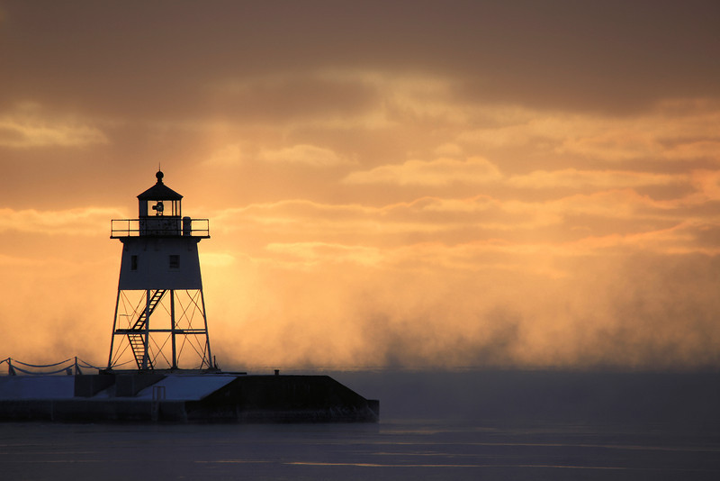 "TUESDAY, JANUARY 3, 2012<br /> <br /> GRAND MARAIS 3501<br /> <br /> ""Steamy winter morning in Grand Marais, MN""<br /> <br /> This photo was taken the morning of January 3, 2012. It was probably the coldest night so far of this winter, so I figured there might be some sea smoke (steam) rising off the lake in the morning. I was right! I headed into Grand Marais to catch the steam as it rose behind the lighthouse. When I first got there I was a little disappointed to see thick clouds and not much color. Soon after the sun rose, however, the clouds started to break up and color started to stream down from the sun, which was hidden behind the clouds along the top edge of this photo.<br /> <br /> Camera: Canon EOS 5D Mark II<br /> Lens: Canon EF 100-400mm<br /> Focal length: 400mm<br /> Shutter speed: 1/125<br /> Aperture: f/8<br /> ISO: 50"