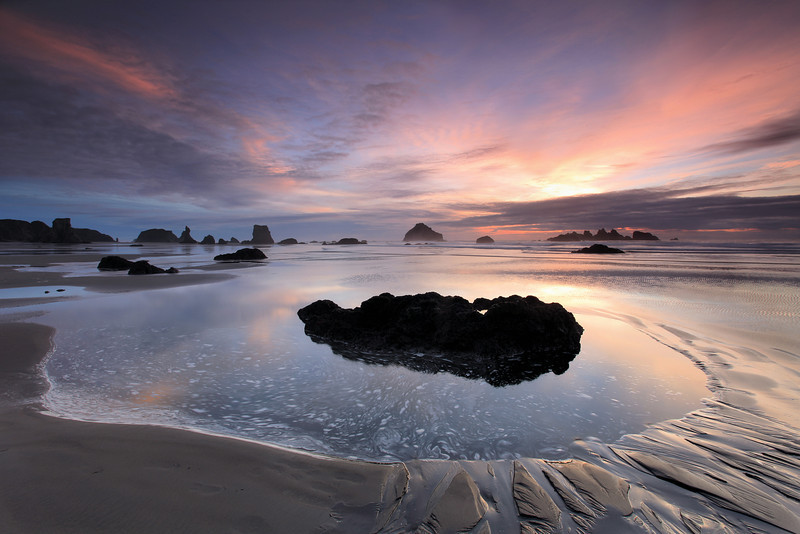 "MONDAY, NOVEMBER 19, 2012<br /> <br /> OREGON 8134<br /> <br /> ""Sunset Tide Pool, Bandon Beach""<br /> <br /> Last week we were out in Oregon and Washington to visit Jessica's family.  While the focus of the trip was to spend time with family, we did make it out here and there to see the sights and get in a little bit of photography time.  This photo is from Bandon Beach in Oregon, one of my favorite areas along the entire coast.  Bandon is a rather well-known beach and a favorite of photographers because of the large variety of ""sea stacks"" that are all along the beach.  At sunset the place is a photographer's paradise, especially on evenings where the tide is low and receding.  Many of the sea stacks were high and dry, others had pools of water around them.  Several were covered with star fish along the bottom edges of the rocks.  We had a glorious sunset during our evening at Bandon. It was one of the highlights of the trip for sure!<br /> <br /> Camera: Canon EOS 5D Mark II<br /> Lens: Canon EF 17-40mm<br /> Focal length: 17mm<br /> Shutter speed: 1.6 seconds<br /> Aperture: f/16<br /> ISO: 50"